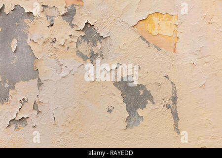 Light brown color, painted wall. Weathered and faded texture, grunge background. Exterior facade of a residential building - Stock Photo