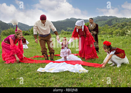 Kazakh people showing local tradition of Tusau Kesu which symbolizes a ceremony that accompanies first steps of a child, Kazakhstan - Stock Photo