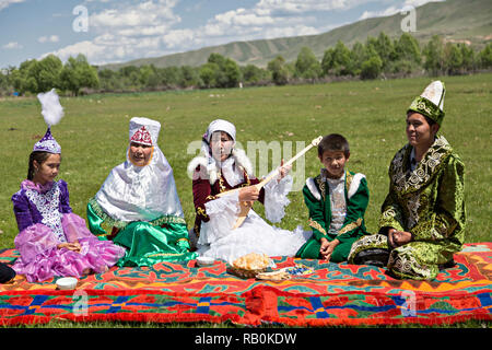 Kazakh family in traditional clothes with a woman singing and playing local instrument of Dombra, Kazakhstan. - Stock Photo