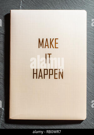 Make It Happen text on notebook on dark background. Concept for doing things and realize ideas. - Stock Photo