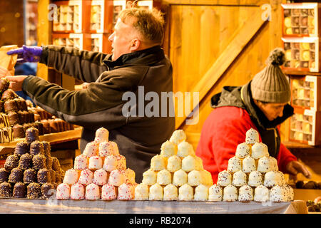 People working on Christmas Market stall, selling chocolates (varieties of chocolate teacakes displayed on counter & in boxes) - York, England, UK - Stock Photo
