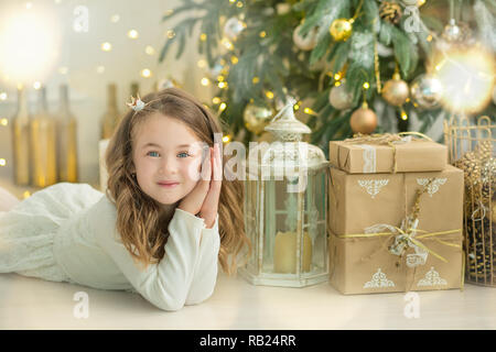 Family on Christmas eve at fireplace. Kids opening Xmas presents. Children under Christmas tree with gift boxes. Decorated living room with traditiona - Stock Photo