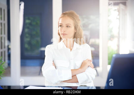 Portrait attractive young businesswoman sitting with arms crossed at office desk behid her laptop and looking deep in thought. - Stock Photo
