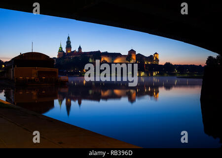 Poland, city of Krakow, view to Wawel Castle at tranquil evening from under the bridge on Vistula River - Stock Photo