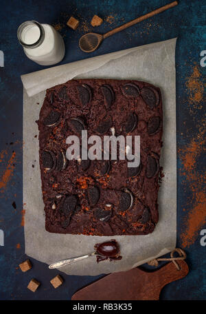 Brownie with oreo cookies and caramel cream on a blue background. view from above - Stock Photo
