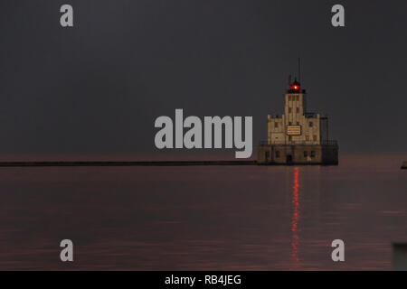 Milwaukee breakwater lighthouse in Milwaukee bay flashes a red light as darkness falls over Lake Michigan in Wisconsin. - Stock Photo