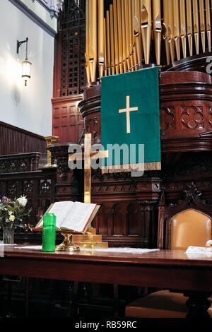 Interior of a protestant church altar with golden cross, holy bible and candles on it. - Stock Photo