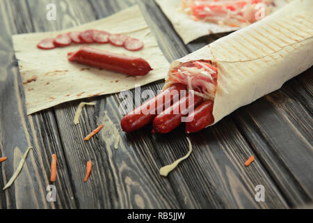 smoked sausage in pita bread on wooden background - Stock Photo