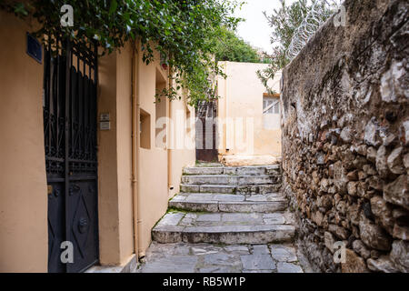 Plaka, Athens Greece. Old town narrow pedestrian streets and stairs, houses facades and stone walls. Low angle, perspective view - Stock Photo
