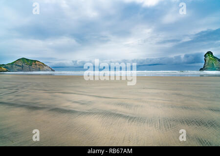 Two small islands on Wharariki Beach on overcast day at low tide in moody atmospheric image - Stock Photo