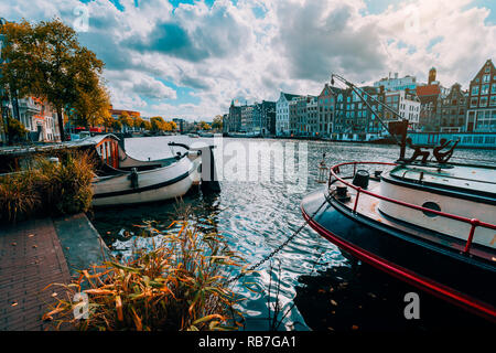 Amsterdam canal Singel with typical dutch houses and houseboats during sunny autumn day. Golden trees and amazing cloudscape. Holland, Netherlands - Stock Photo