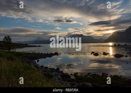 Romantic sunset of the midnight sun behind the mountains and sea on the Lofoten islands in Norway, Europe. Taken north of Henningsvær, Vågan, Nordland - Stock Photo