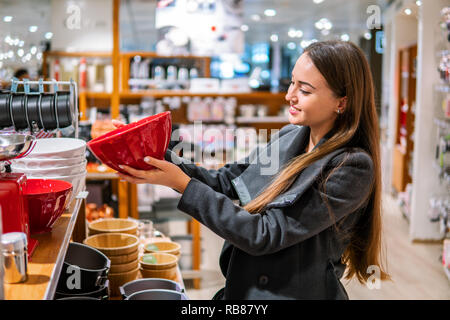 woman choosing utensil dishes in a store supermarket - Stock Photo