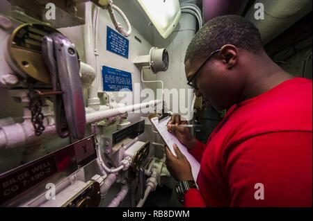 ATLANTIC OCEAN (Dec. 10, 2016) Petty Officer 3rd Class Osada Allen, from Brooklyn, New York, inspects a passageway aboard the aircraft carrier USS George Washington (CVN 73). George Washington, homeported in Norfolk, is underway conducting carrier qualifications in the Atlantic Ocean. - Stock Photo