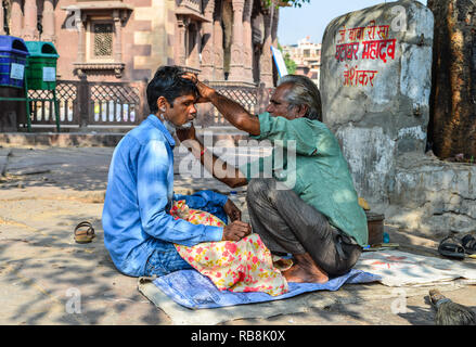 Jodhpur, India - Nov 6, 2017. A man gets a shave at a street barber shop in Jodhpur, India. Jodhpur is the second largest city in state of Rajasthan. - Stock Photo