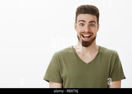 Close-up shot of excited and suprised amazed happy bearded man raising eyebrows and widen eyes smiling broadly at camera as receiving unexpected awesome offer of lifetime over white background - Stock Photo