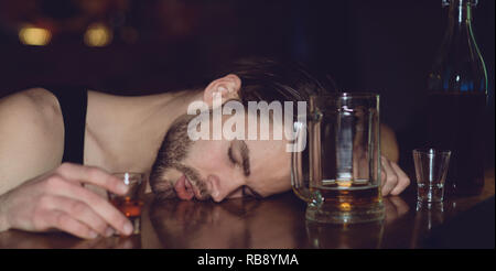 Alcohol abuse. Man sleep after drinking strong alcoholic beverage and beer in pub. Alcoholic man sleeping at bar counter. Alcohol addict with alcohol drink. Alcohol addiction and bad habit - Stock Photo