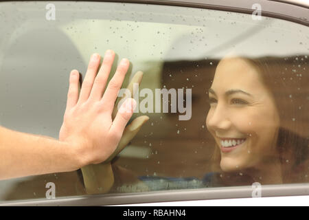 Happy couple or friends saying good bye touching hands through a car window before travel - Stock Photo