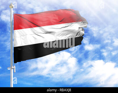 National flag of Yemen on a flagpole in front of blue sky. - Stock Photo