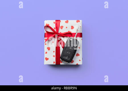 Give gift car key concept top view. Present box with red ribbon bow, heart and car key on purple colored background. - Stock Photo