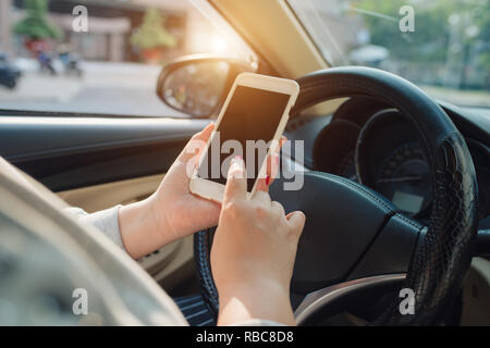 Young female driver using touch screen smartphone and hand holding steering wheel in a car. - Stock Photo