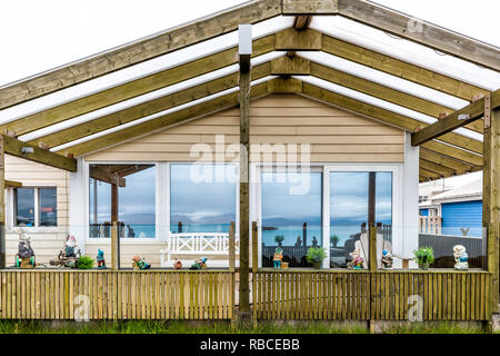 Hofn, Iceland - June 15, 2018: Closeup of wooden house in small fishing village with reflection of blue fjord river water - Stock Photo