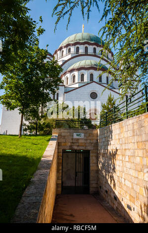 Belgrade, Serbia - June 09, 2013: Famous Saint Sava church exterior facade architecture surrounded by vibrant green spruce trees and entrance to publi - Stock Photo