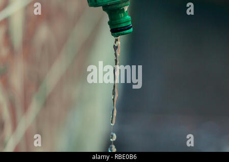 Water dripping from a faucet in the yard - Stock Photo