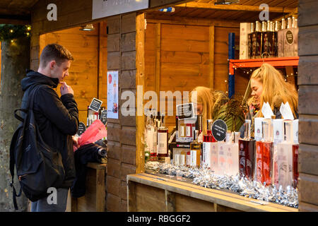 People working at stall selling Brittain's gin & vodka & potential customer at Christmas Market looking at price list on display - York, England, UK. - Stock Photo