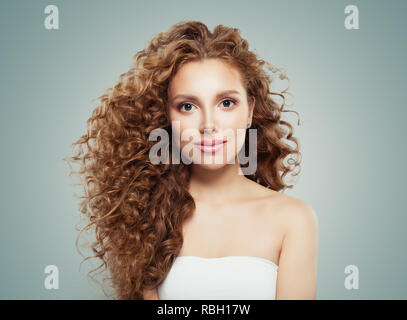 Young beautiful model woman with long healthy hairstyle on gray background - Stock Photo