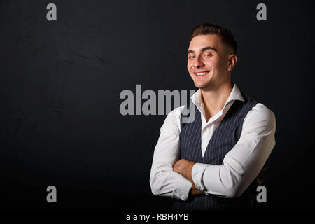 Portrait of young handsome man wearing white shirt standing on the gray background and laughing - Stock Photo