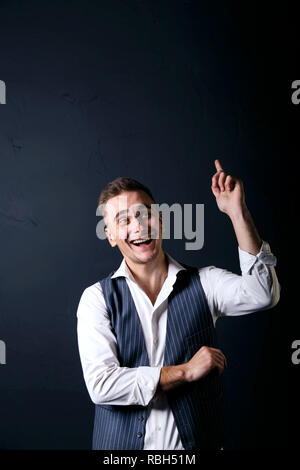 Portrait of young handsome man wearing white shirt standing on the gray background, rejoicing and raised thumbs up - Stock Photo