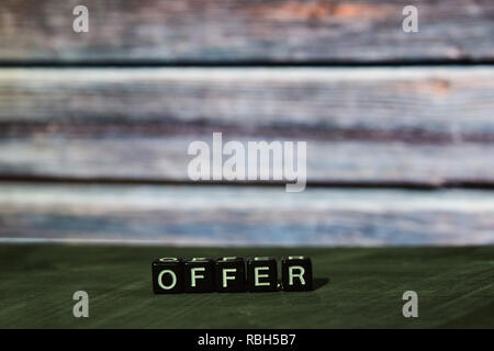 Offer on wooden blocks. Cross processed image with bokeh background - Stock Photo