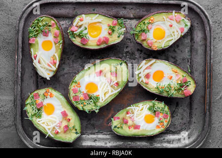 Keto diet dish: Avocado boats with ham cubes, quail eggs, cheese and cress sprouts on metal tray - Stock Photo