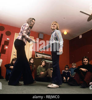 Teenage party in the 1970s. A group of teenagers have arranged a party and a boy and a girl is dancing to the music from the jukebox. Notice the wide legged jeans type that was typical of the decade. Sweden 1970s. Photo Kristoffersson - Stock Photo