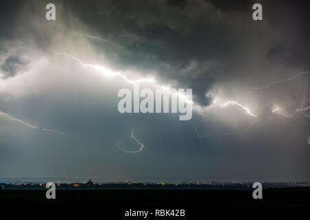 Lightnings over city during thunderstorm - Stock Photo