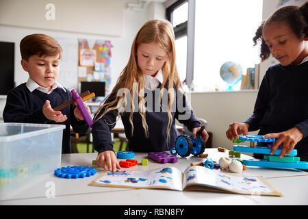 Three primary school children  working together, following an instruction book and using construction blocks in a classroom, front view, close up - Stock Photo