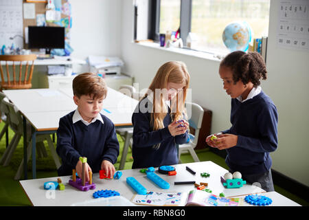Elevated view of three primary school kids working together using construction blocks in a classroom - Stock Photo