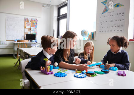 Female teacher and three primary school kids sitting at a table in a classroom working with educational construction toys - Stock Photo
