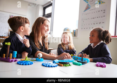 Female teacher and three primary school kids sitting at a table in a classroom working with educational construction toys, close up, low angle - Stock Photo