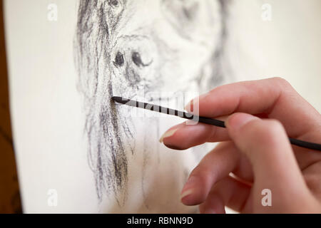 Close Up Of Artist Sitting At Easel Drawing Picture Of Dog In Charcoal - Stock Photo