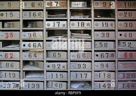 Old vintage metal made, ruined traditional chinese empty or full mailboxes / letter box with number sign in hongkong village - Stock Photo