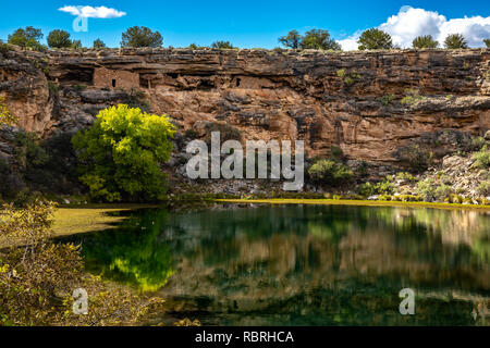 Ancient ruins and surroundings reflect on the quiet water of Montezuma Well. Part of Montezuma Castle National Monument. - Stock Photo