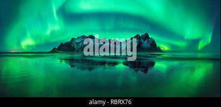 Aurora reflections on Stokksnes black beach with Vestrahorn mountains in center, Iceland - Stock Photo