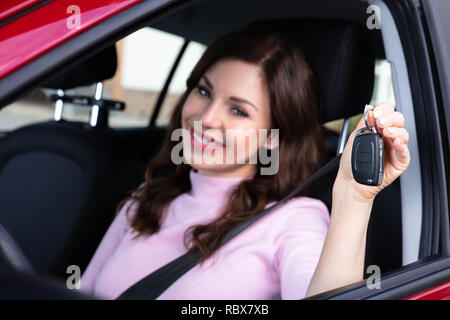 Close-up Of A Happy Young Woman Sitting Inside Car Showing Key - Stock Photo
