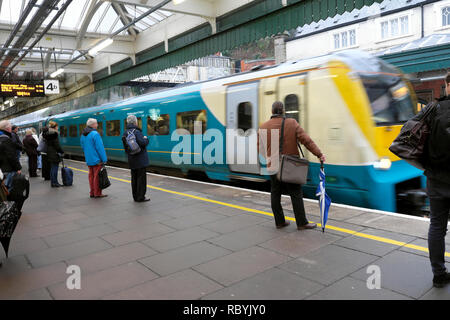 Shrewsbury train station a moving train approaching people waiting on platform waiting to get on to travel to Manchester UK England KATHY DEWITT - Stock Photo