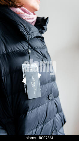 PARIS, FRANCE - FEB 2, 2018: Side view of woman wearing Max Mara Weekend Italian buy new fashionable down jacket reading price tag and logo - Stock Photo