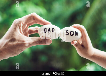 Eggs with inscriptions father and son. Problems between father and son concept. - Stock Photo