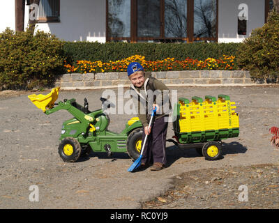Little boy playing with toy-tractor - Stock Photo