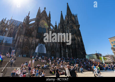 Cologne, Germany - May 2018. Local people and tourists sitting on the steps of the Cathedral and walking in the square in front of the Central Station - Stock Photo